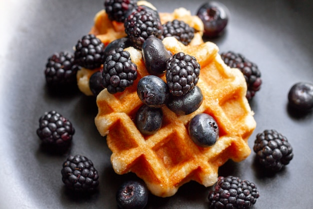Flat pone frutas del bosque negro en waffles