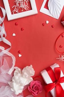 Flat yacía en el día de san valentín con. regalo, sobre, corazón y corazones, ángel, marco y rosa sobre fondo rojo.