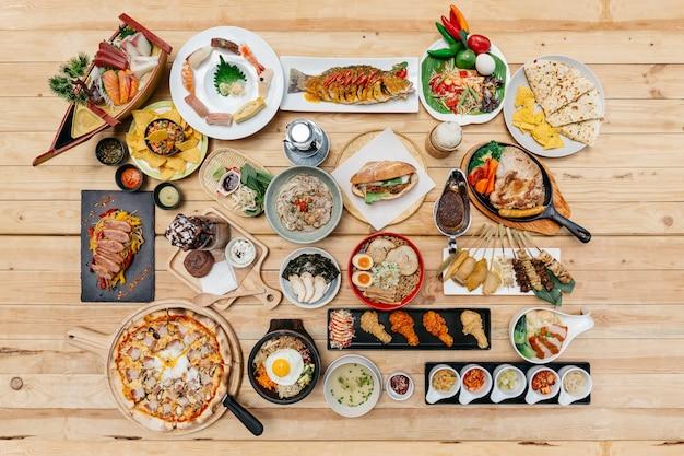 Flatlay de alimentos internacionales en mesa de madera.