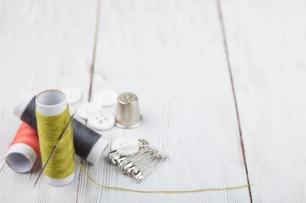 Flatlay de coser y adaptar instrumentos sobre fondo de madera blanco