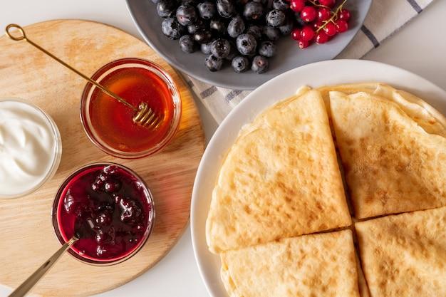 Flatlay de cuatro crepas caseras dobladas, grosellas y moras frescas y tres tazones pequeños con mermelada, miel y crema agria