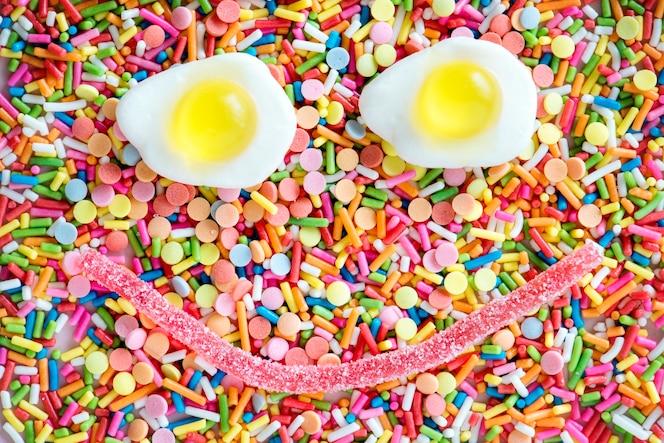Flatlay de huevos fritos de gelatina formando una cara sonriente y rocía textura de fondo