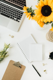 Flatlay de espacio de trabajo moderno con laptop y ramo de girasoles en blanco