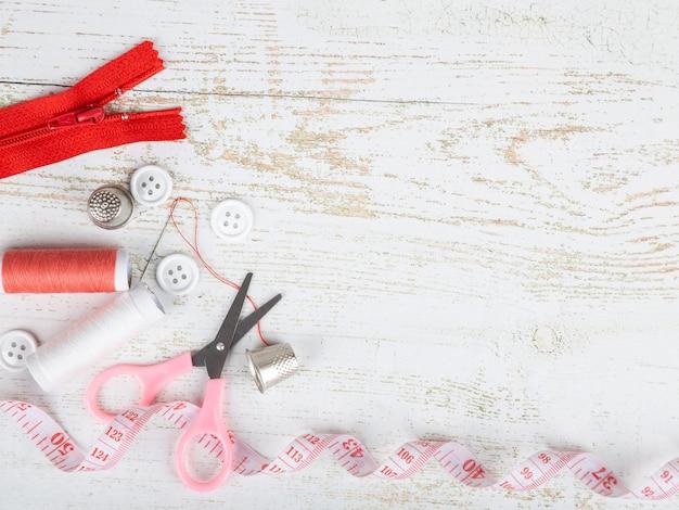 Flatlay de herramientas para la costura y costura sobre fondo de madera blanco