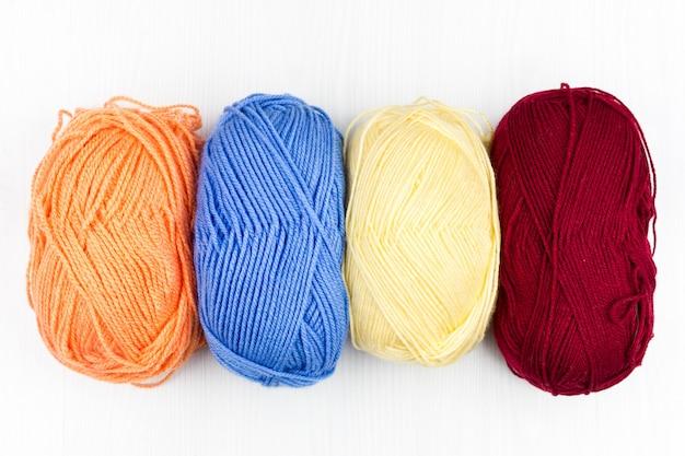 Flatlay de madejas de tejido multicolor pastel de hilo y agujas de tejer sobre fondo blanco