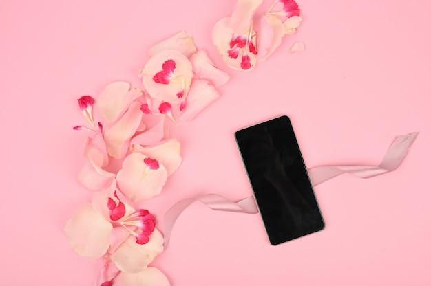 Flatlay con maqueta de smartphone y estampado de flores en el espacio rosa. concepto de compras de primavera. vista superior.