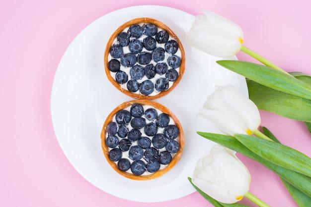 Flatlay plano laico encima de la foto de primer plano de ángulo alto de delicioso postre de confitería azucarada en un plato blanco claro con flores florales blancas como la nieve superficie pastel aislada