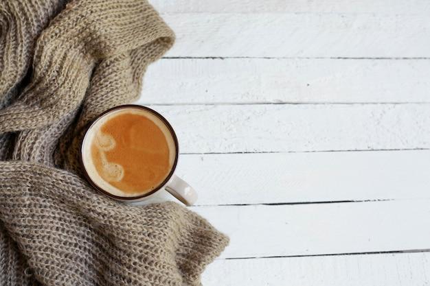 Flatlay con taza de café en bufanda en madera blanca