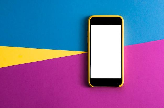 Flatlay con teléfono inteligente en tres tonos de color amarillo, violeta y azul claro de fondo