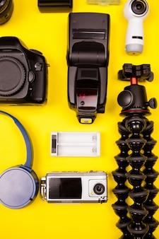 Flatlay de vista superior del kit de fotógrafo de vacaciones de verano sobre fondo amarillo