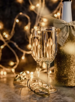 Flauta de champán con botella brillante en oscuridad con luces