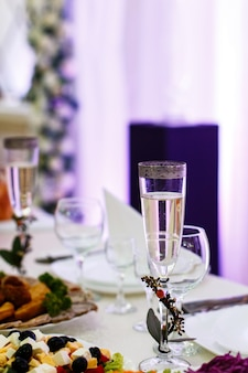 La flauta de champán decorada con ramas pequeñas se encuentra en la mesa