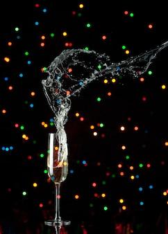 Flauta de champán con salpicaduras y luces de colores