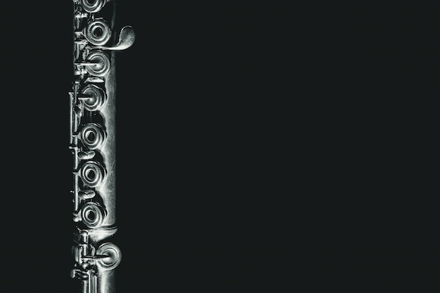 Flauta clásica de primer plano sobre fondo negro con espacio de copia.