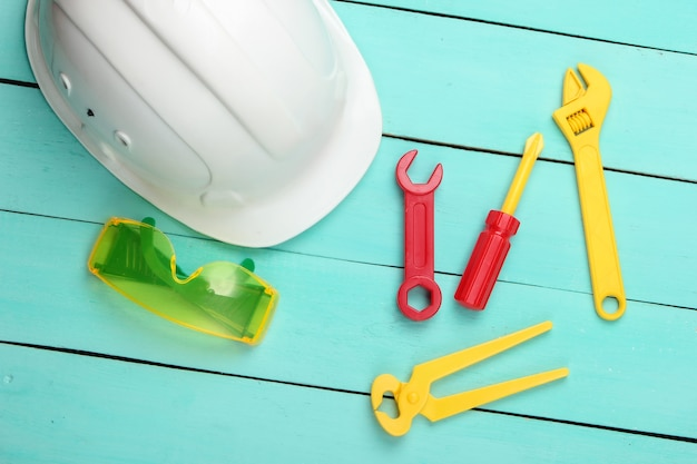 Flay lay composición de herramientas de trabajo para niños y casco en madera azul.