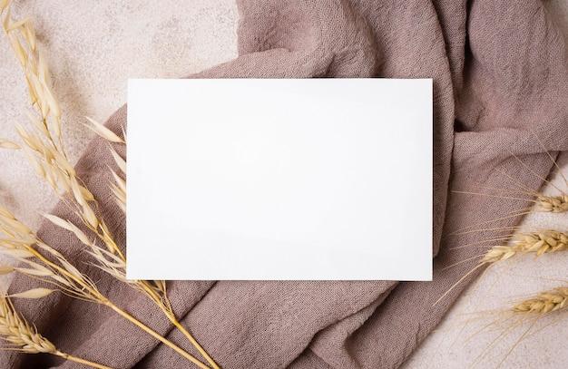 Flay lay de papel con plantas otoñales y textiles.