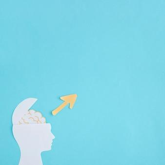 Flecha amarilla direccional sobre el recorte de papel cerebro abierto sobre fondo azul