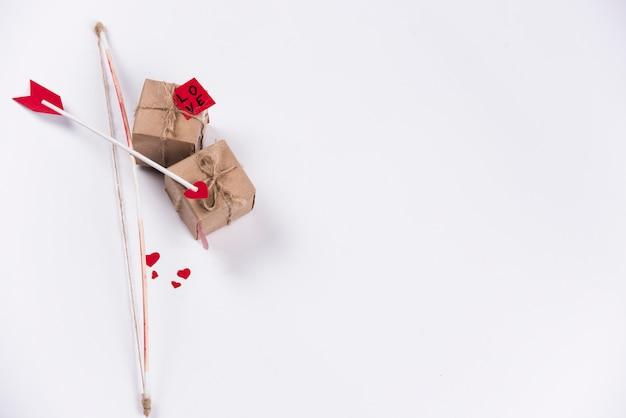 Flecha de amor con arco y cajas de regalo en mesa