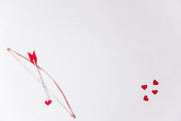 Flecha de amor con lazo en la mesa.