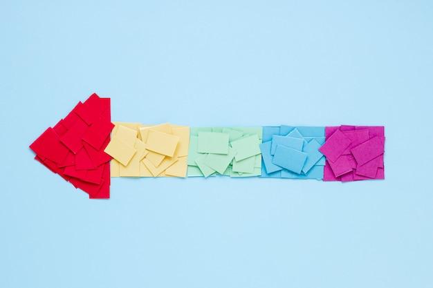 Flecha arcoiris hecha de papeles brillantes
