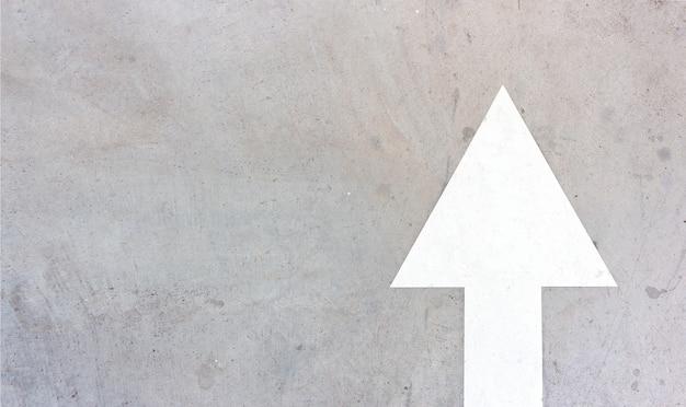 Flecha blanca vieja en el fondo del camino de cemento