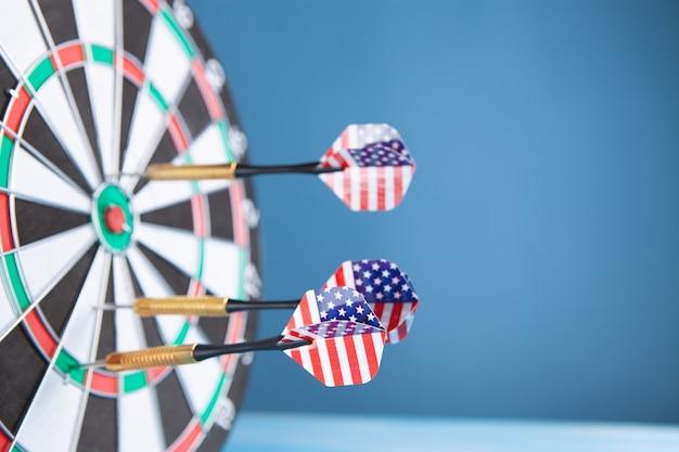 La flecha del dardo golpea en el centro del objetivo del tablero de dardos.