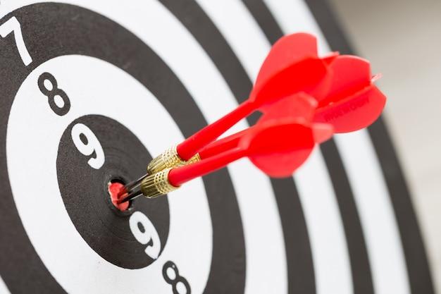 Flecha de dardo objetivo golpeando en el centro del tablero de dardos