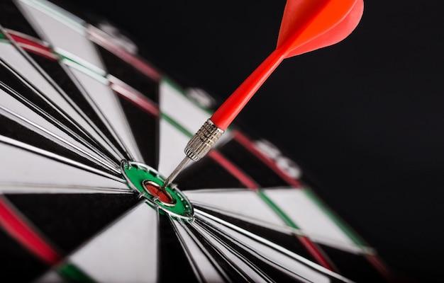 Flecha de dardo rojo en el centro del tablero de dardos. concepto de objetivo empresarial, éxito y triunfo.