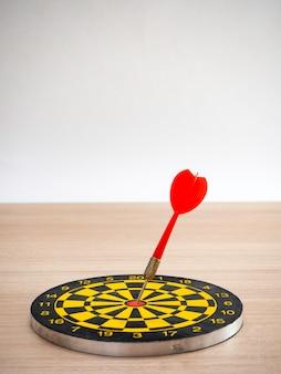 Flecha de dardo y tablero de dardos sobre fondo de madera marrón