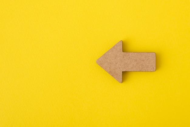 Flecha de madera sobre fondo amarillo. indicador de dirección.
