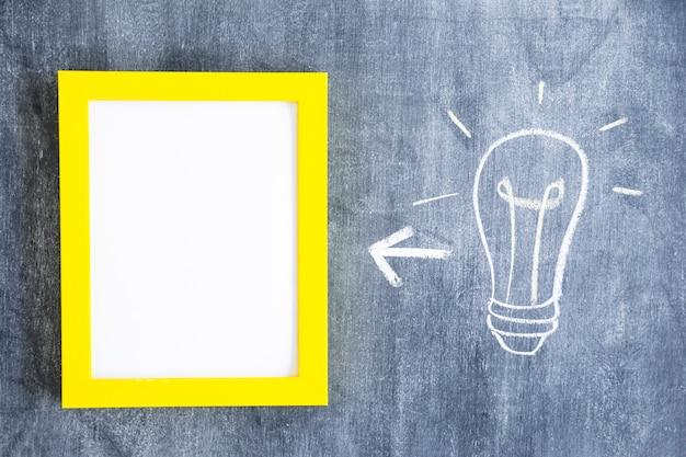 Flecha entre marco blanco con borde amarillo y bombilla de luz en la pizarra