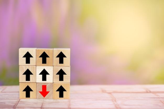 Flecha roja del bloque de madera apuntando en sentido contrario al disruptivo de las flechas negras en la mesa de madera.