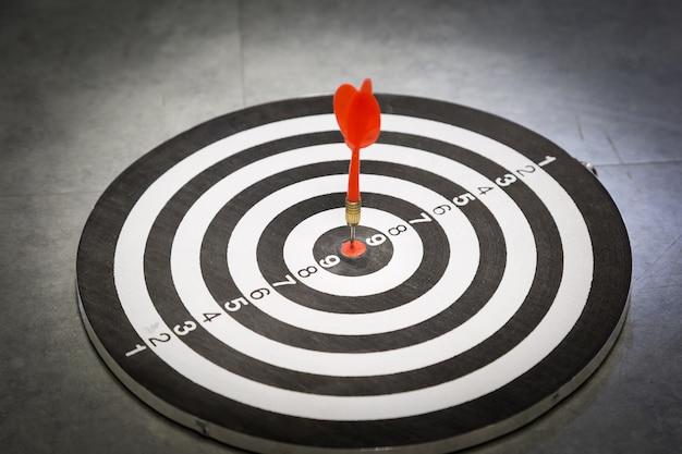La flecha roja del dardo golpea en el centro del blanco del tablero de dardos.