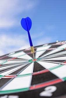 Flecha roja del dardo golpeando en el centro del blanco del tablero de dardos con el fondo del cielo azul