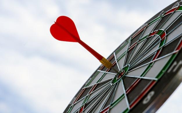 Flecha roja de dardo golpeando en el centro de destino del marketing de tablero de dardos