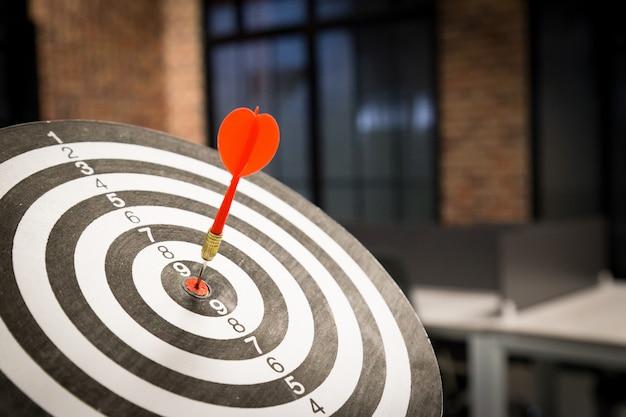 Flecha roja del dardo que golpea en el centro objetivo.