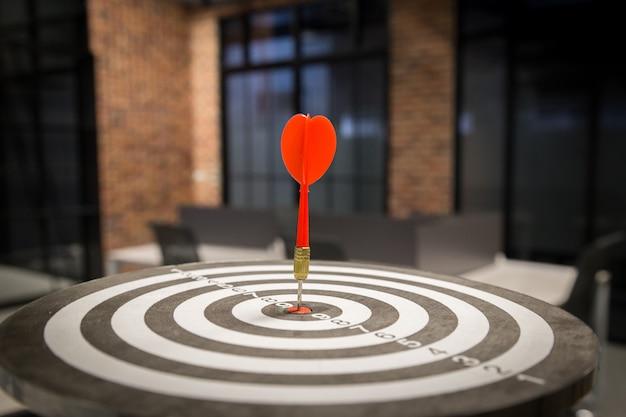 Flecha roja de dardos que golpea en el centro de destino del tablero de dardos en la diana