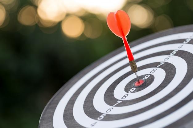 Flecha roja de destino de dardos que golpea la diana con el concepto de marketing de objetivos y éxito empresarial
