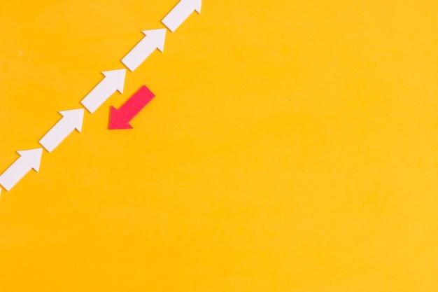 Flecha roja rebelde y multitud de flechas blancas con espacio de copia