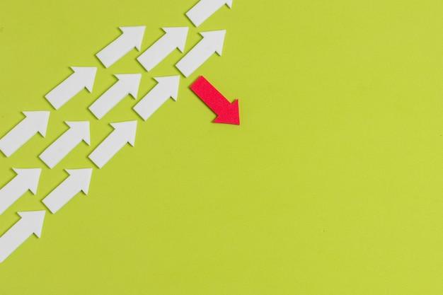 Flecha roja rebelde y multitud de flechas blancas sobre fondo verde