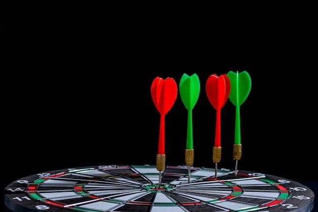 La flecha roja y verde del dardo golpea el centro del blanco