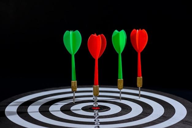 La flecha roja y verde del dardo que golpea el centro del objetivo es el tablero de dardos aislado sobre fondo negro