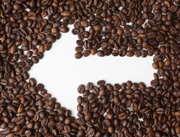 Flecha a través de granos de café apuntando a la izquierda