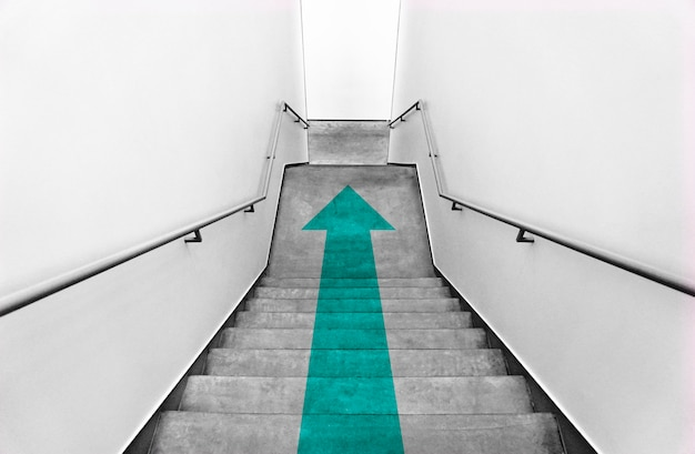 Flecha verde azulado en escaleras grises