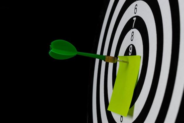 La flecha verde del dardo golpea en el centro de destino del tablero con papel de texto.