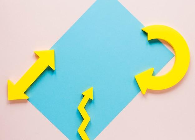 Flechas amarillas planas y maqueta de cartón azul sobre fondo rosa