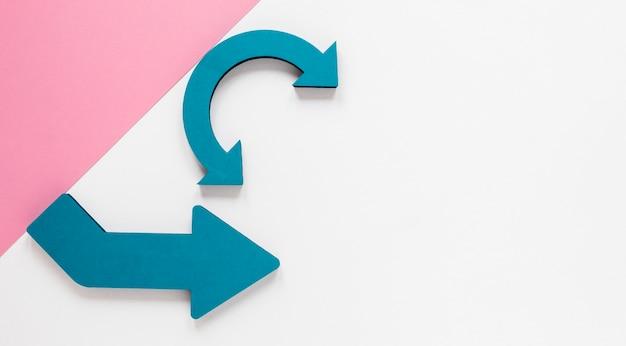 Flechas azules planas y cartón rosa sobre fondo blanco con espacio de copia