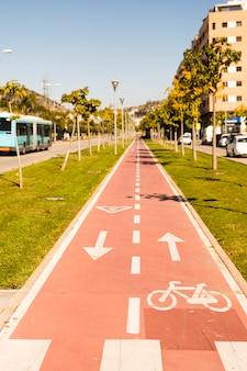 Flechas direccionales y signo de bicicleta en carril de ciclo de perspectiva en disminución