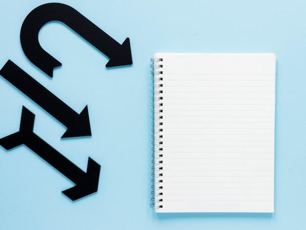 Flechas negras planas y maqueta de cuaderno sobre fondo azul