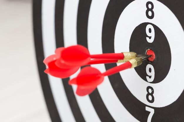 Flechas que golpean el centro de un tablero objetivo, concepto de asociación